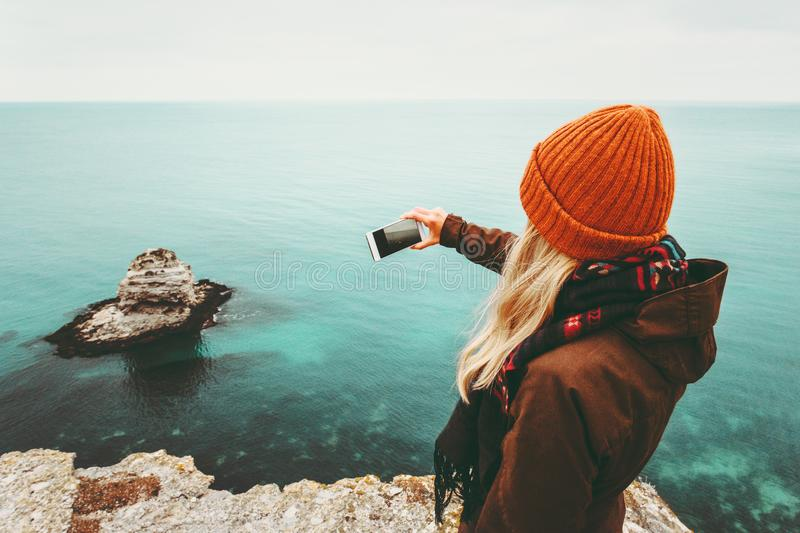 Woman taking photo by smartphone of cold sea view royalty free stock photo