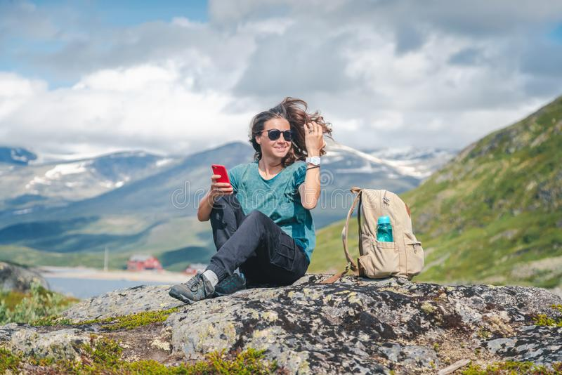 Woman  taking photo by smartphone exploring mountains in Norway adventure , vacations traveling lifestyle modern technology royalty free stock photo