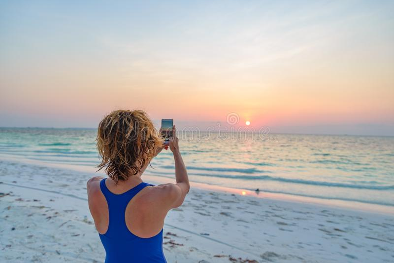 Woman taking photo with smartphone of romantic sky at sunset on sand beach, rear view, real people traveling around the world. stock image