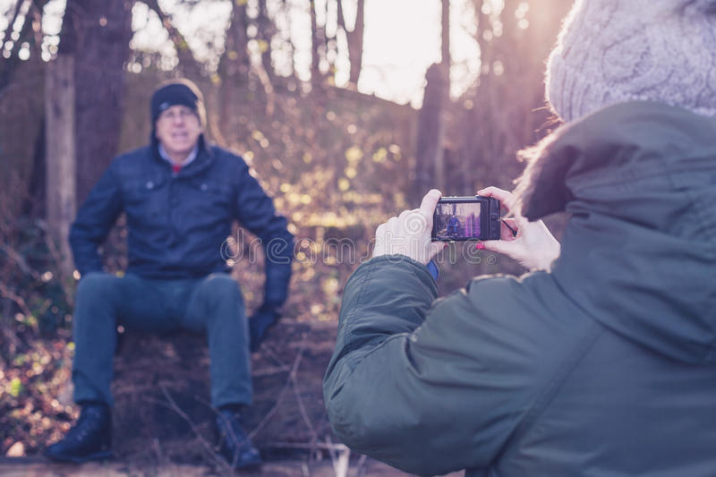 Woman taking photo of snior man in forest royalty free stock images