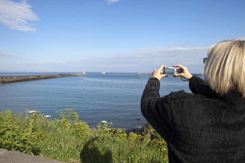 Woman taking photo in Whitley Bay stock photo