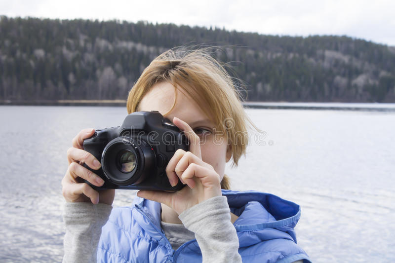 Woman Taking Photos with Camera. Young woman is standing by the water, holding camera in hands and taking photos royalty free stock images