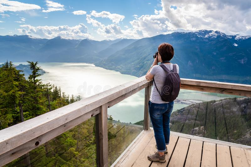Woman Taking Photos with her DSRL Camera from the Top of a Mountain. Woman Hiker Taking Pictures from a Viewing Platform on the Top of a Mountain overlooking an stock photo