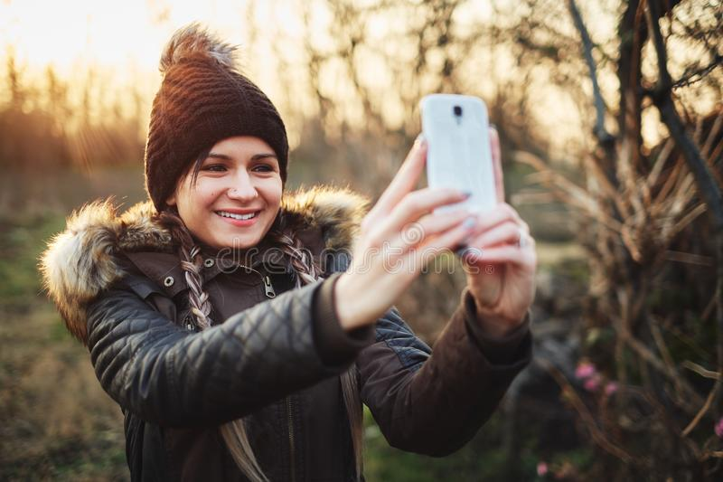 Woman taking photos with smartphone. Young attractive woman taking photos with smartphone royalty free stock images