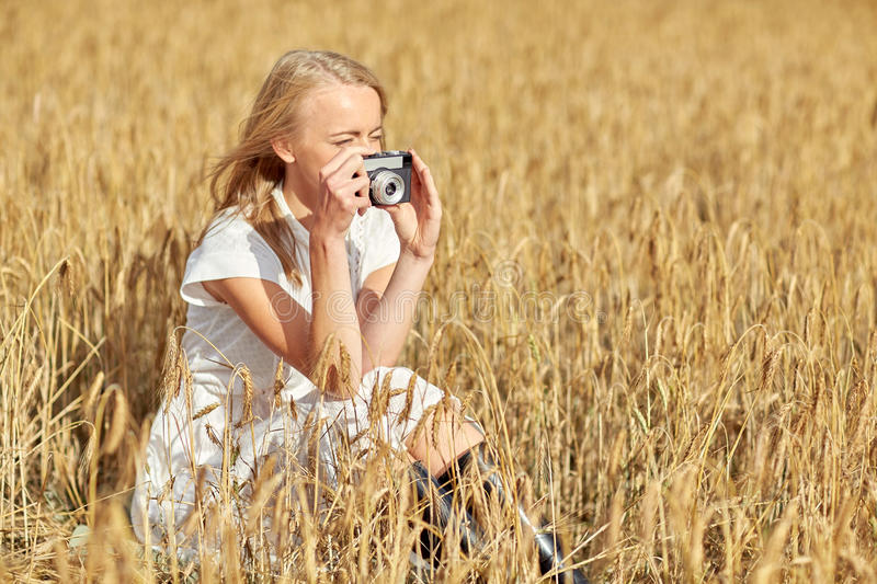 Woman taking picture with camera in cereal field stock photo