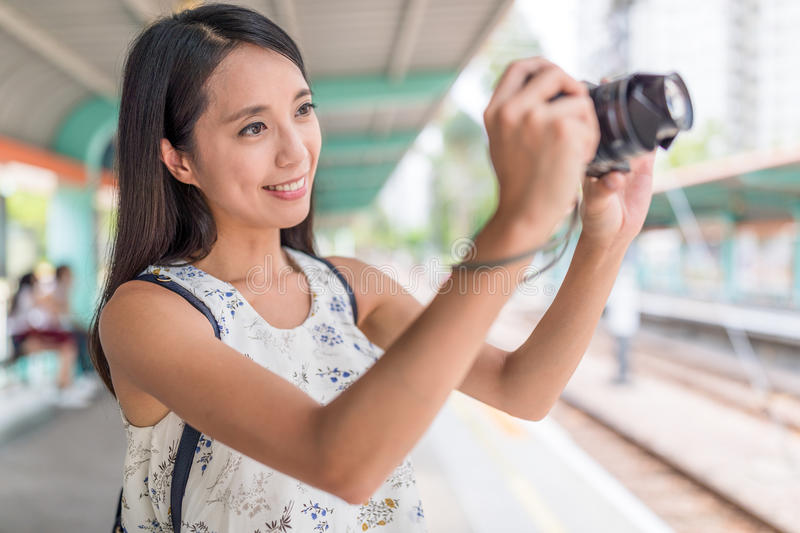 Woman taking picture with camera in light rail station. Asian young woman royalty free stock image