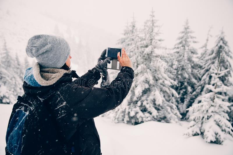 Woman taking a picture with her smartphone of the beautiful winter landscape in the mountains stock image