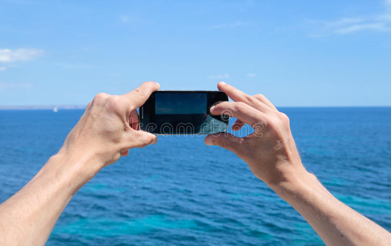 Woman taking a picture using her smartphone. A woman takes a picture by the sea using her mobile phone in palma de mallorca, on the spanish balearic island stock photos