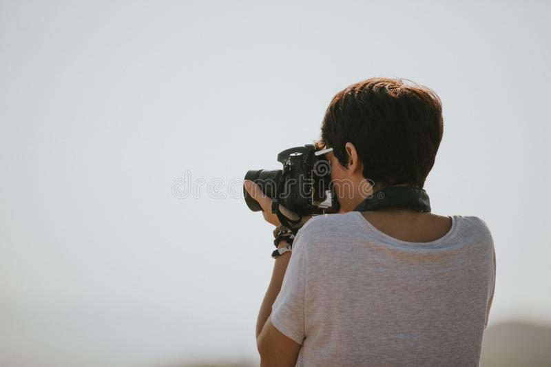 Woman in t-shirt taking a photo with a dslr camera in nature with daylight. royalty free stock image