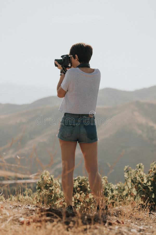 Woman in t-shirt taking a photo with a dslr camera in nature with daylight. royalty free stock photo