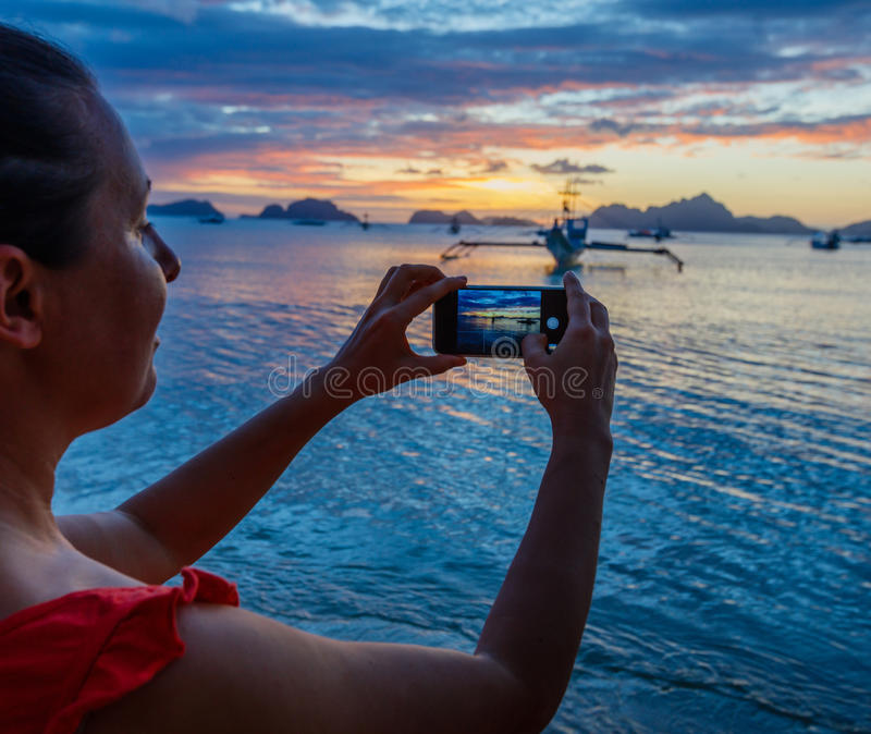 Woman taking pictures at sunset stock photos