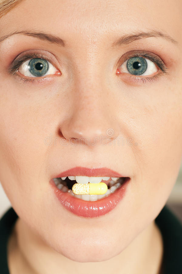 Woman taking a pill royalty free stock photography