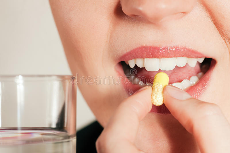 Woman taking a pill royalty free stock images