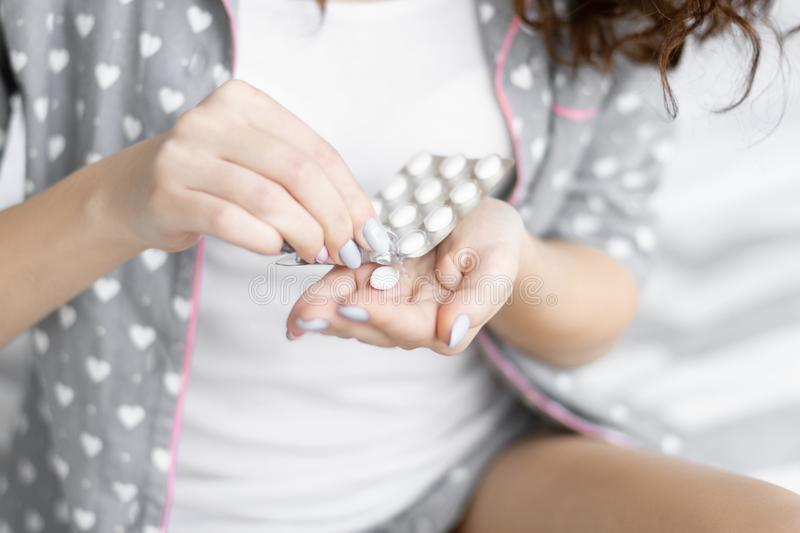 Woman taking pills / medicine in grey pajamas stock image