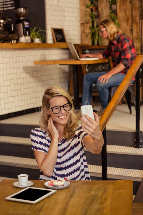 Woman taking a selfie. In the cafe royalty free stock photo