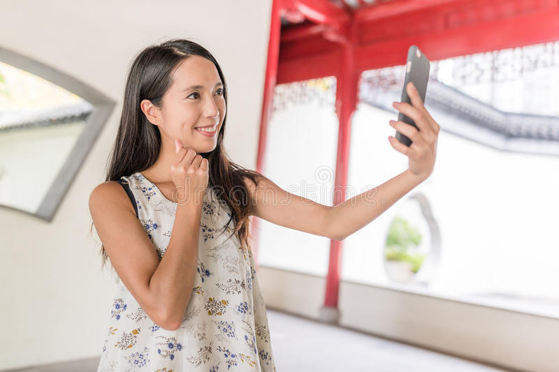 Woman taking selfie in chinese garden. Asian young woman royalty free stock image
