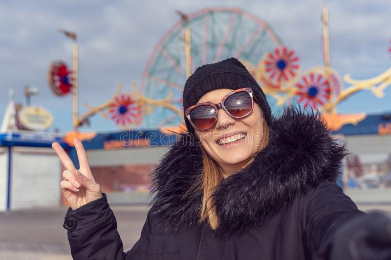 Woman taking a selfie in coney island. Luna park as background stock photography