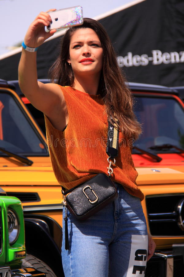 Woman taking selfie. Dutch fashionista taking a selfie with the new cars at the mercedes benz fashion week amsterdam 2017. Wearing her outfit of the day.. Taken royalty free stock image