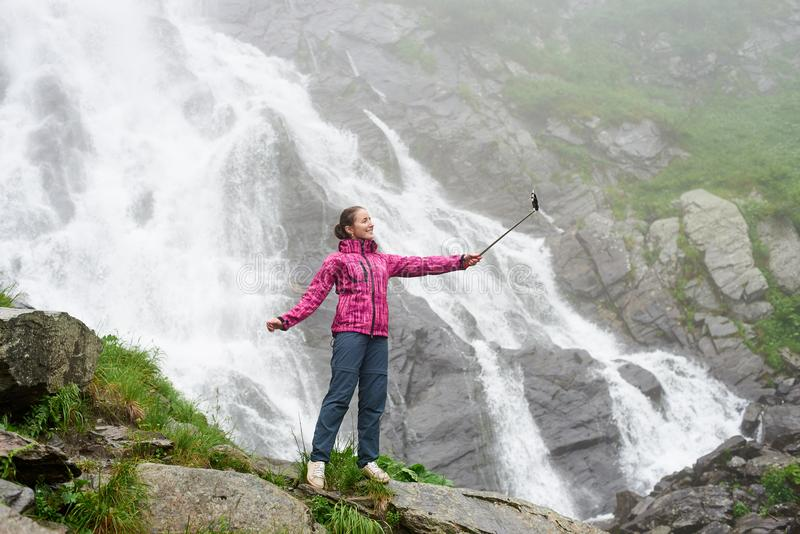 Woman taking a selfie in front of big waterfall. stock image