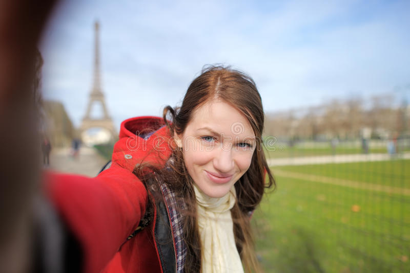 Woman taking selfie near the Eiffel tower stock photo