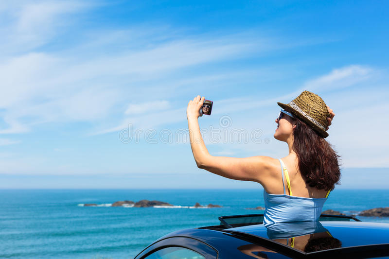 Woman taking selfie photo on car summer travel. Happy woman taking selfie photo with smartphone camera on car summer travel vacation to the coast. Brunette girl royalty free stock photos