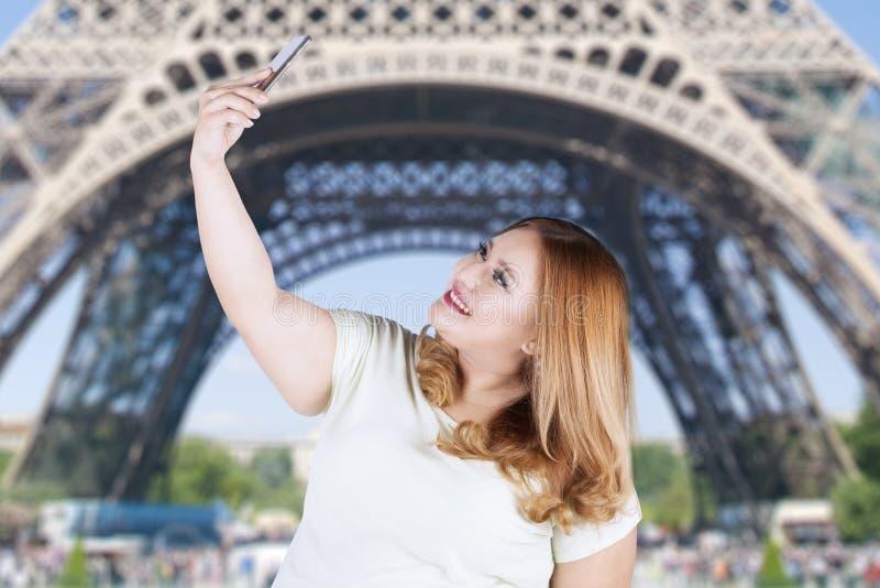 Woman taking selfie photo at eiffel tower stock photo