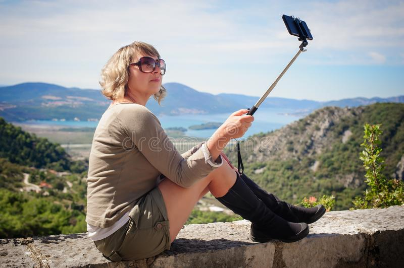 Woman taking selfie picture on landscape background using photo stock photo