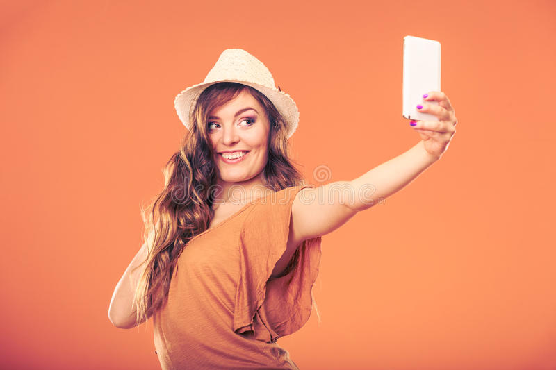 Woman taking selfie self picture with smartphone. Happy fashionable woman in hat taking selfie self picture with smartphone camera. Summer vacation holiday royalty free stock photo