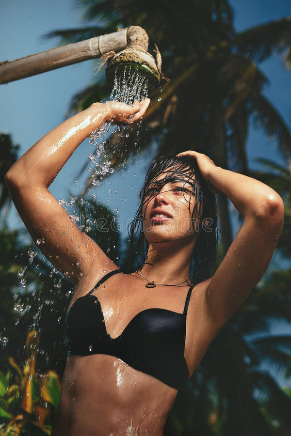 Woman taking a shower outdoors stock photo