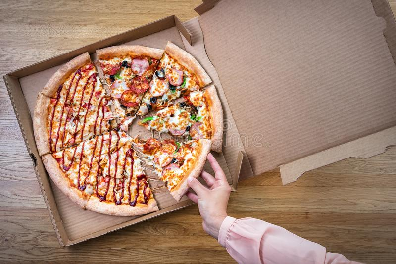 Woman taking slice of delicious pizza from cardboard box. Top view on brown wooden table stock photo