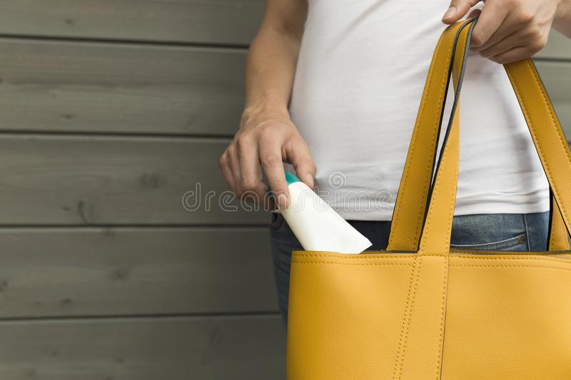 Woman taking sun screen, hand cream out of yellow purse. Sun pro royalty free stock image