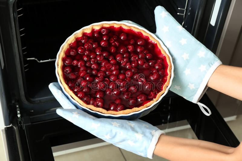 Woman taking tasty cherry pie out of oven stock photography