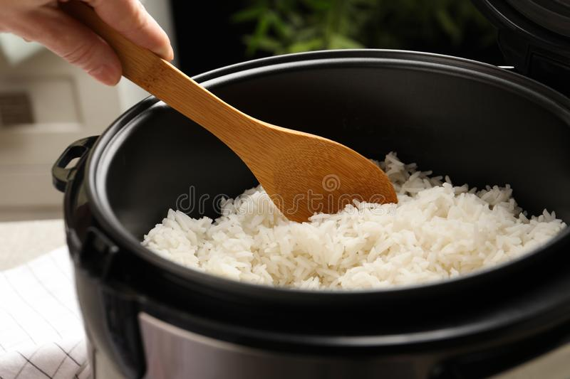 Woman taking tasty rice with spoon from cooker in kitchen stock images