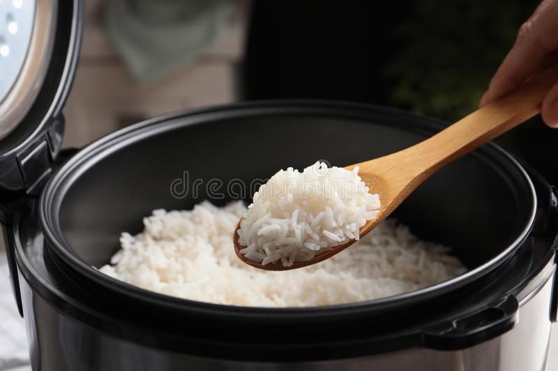 Woman taking tasty rice with spoon from cooker in kitchen royalty free stock image