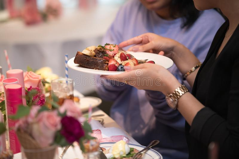 Woman taking toast with fruit salad in a restaurant and talking with her friend. royalty free stock images