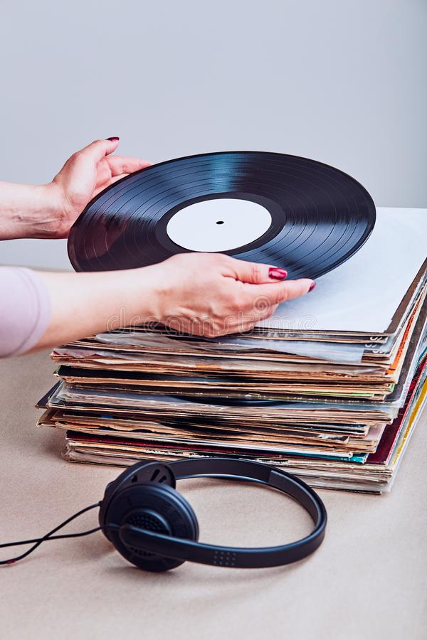 Woman taking vinyl from stack of vinyl records royalty free stock photos