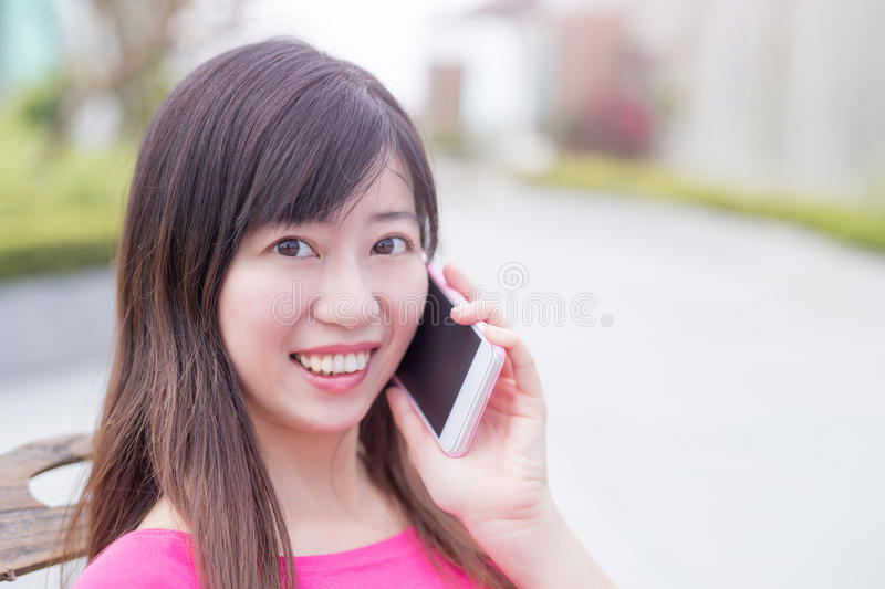 Woman talk on phone. Happily in the park royalty free stock image