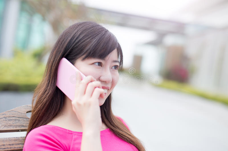 Woman talk on phone. Happily in the park stock photo