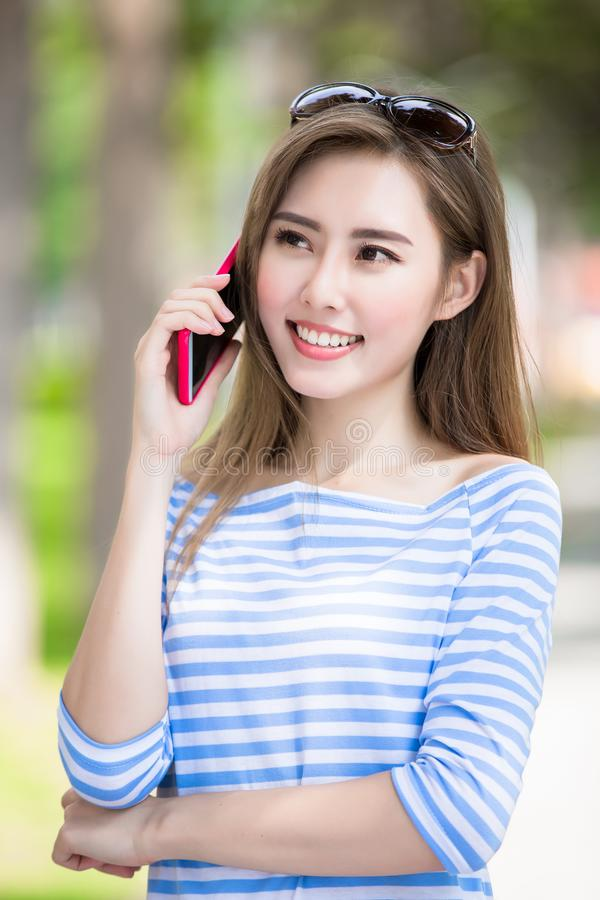Woman talk on phone. In the park stock photography