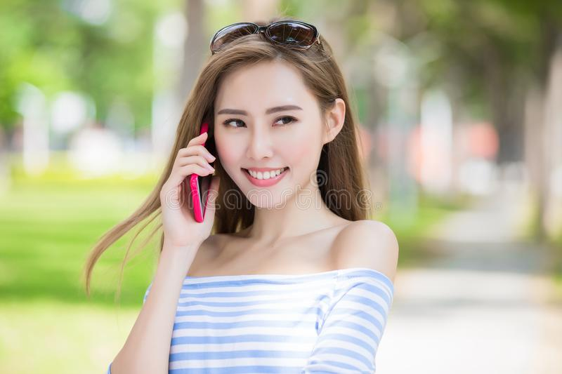 Woman talk on phone. In the park stock photo