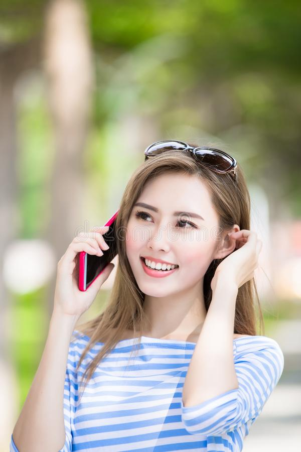 Woman talk on phone. In the park royalty free stock photo