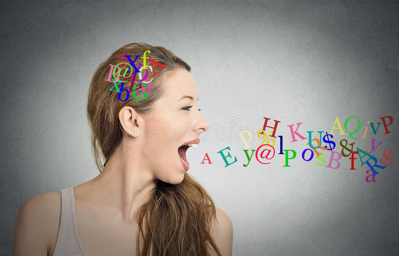 Woman talking, alphabet letters in her head coming out of mouth royalty free stock images