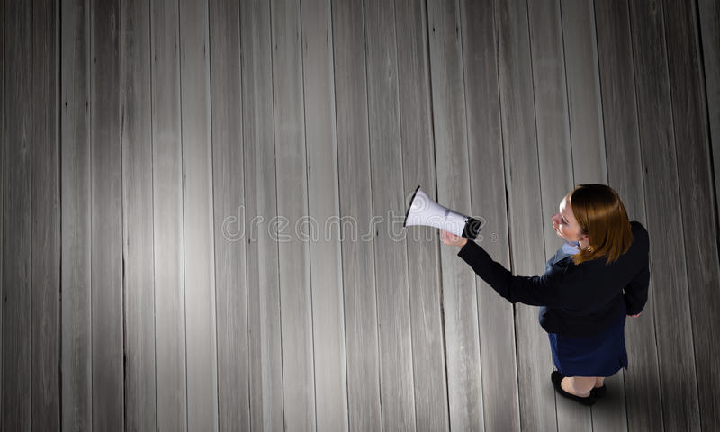 Woman talking in bullhorn. Top view of businesswoman with megaphone in hand stock photo