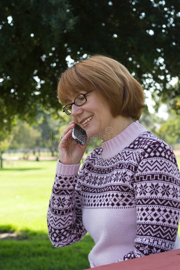 Woman talking on cell at park royalty free stock photos