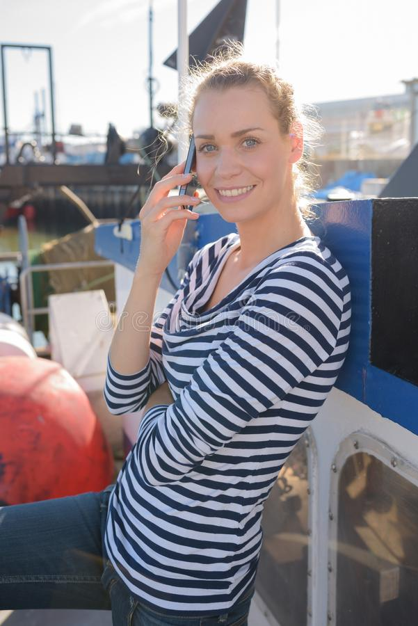 Woman talking on cellphone on seaport. Woman talking on her cellphone on a seaport stock photo
