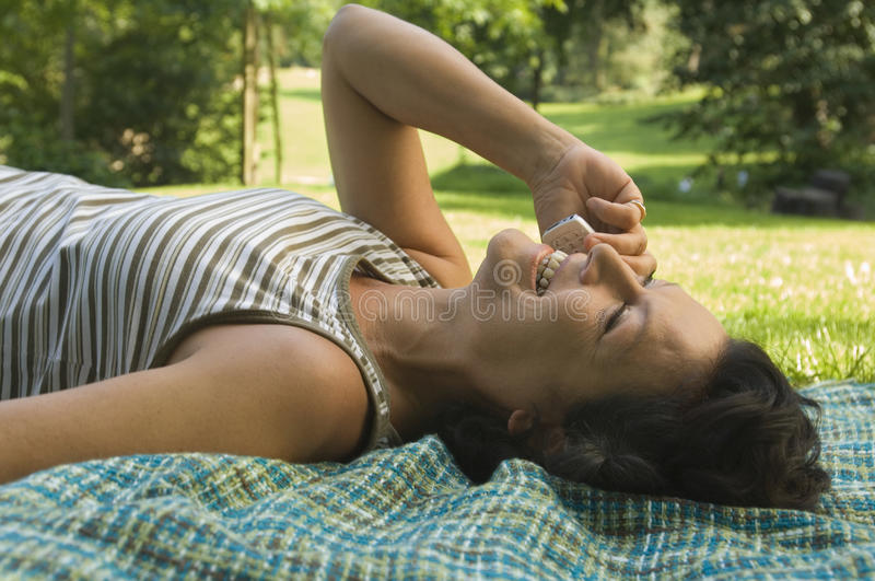 A woman talking on her cell phone. A woman talking on her cell phone, laying on a blanket on the grass stock photo