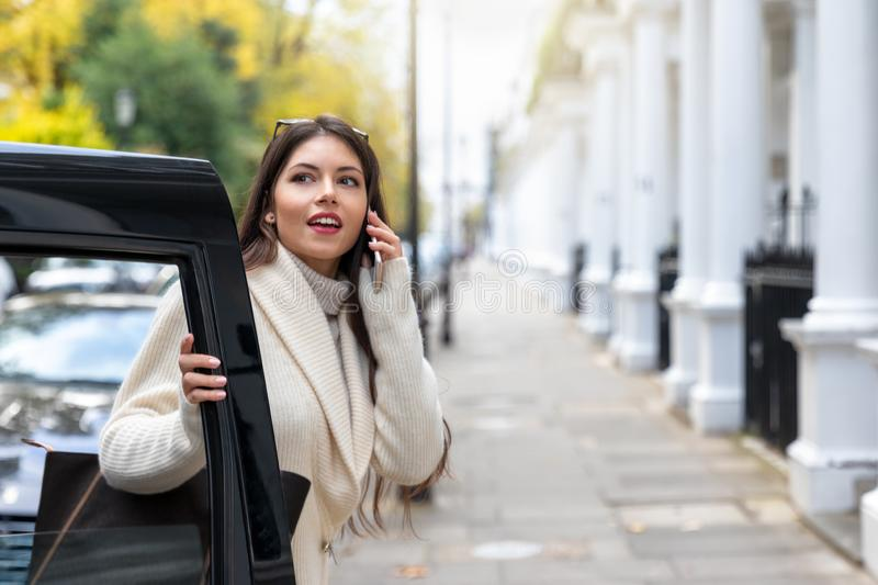 Woman talking on her mobile phone whilst steps off a black cab taxi in London, UK stock images