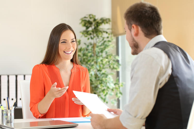 Woman talking in a job interview. Confident women and interviewer looking each other and talking during a job interview at office royalty free stock image