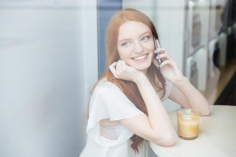 Woman talking on mobile phone and drinking coffee in cafe royalty free stock photos