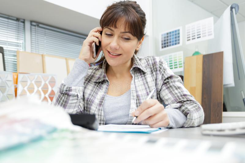 Woman talking on mobile phone in office stock images